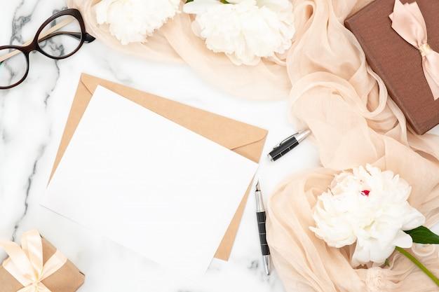 Hochzeitseinladungskarte und kraftpapierumschlag des draufsichtfreien raumes mit weißen pfingstrosenblumen und beige pastellschal.