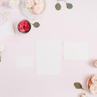 Hochzeitseinladungskartenschablone, rosa und rote rosenblütenknospen und weiße nelke auf hellem pastellrosa