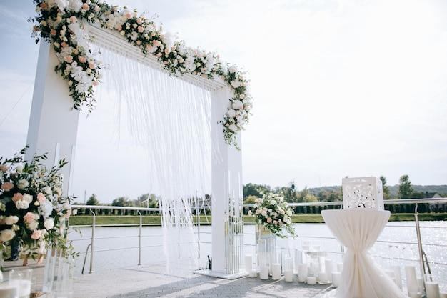 Hochzeitseinrichtung, hochzeitsempfang im freien mit bogen am ufer des sees