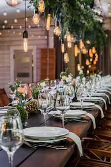 Hochzeitsempfangstisch mit edison-glühbirnen und dekor des grüns.