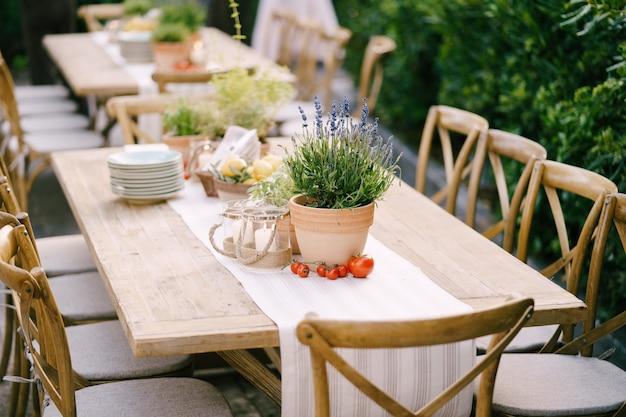 Hochzeitsessen tischempfang bei sonnenuntergang außerhalb der alten rechteckigen holztische mit lappenläufer
