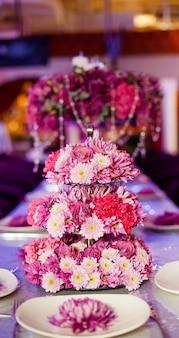Hochzeitsfesttabellenblumen auf dem tisch.