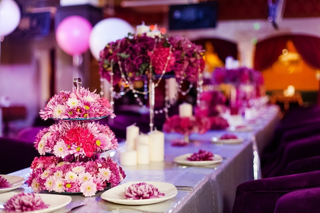 Hochzeitsfesttabellenblumen und weiße kerzen auf dem tisch.