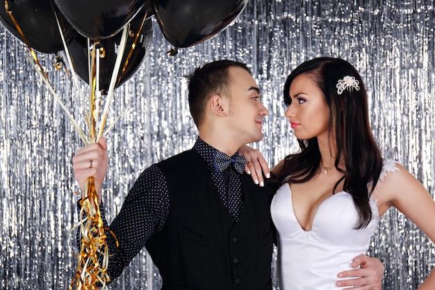 Hochzeitsfoto. junges paar mit schwarzen kugeln auf glitzerndem hintergrund
