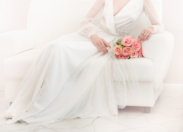 Hochzeitsfoto mit weißem kleid und rosa rosenstrauß auf hellem hintergrund