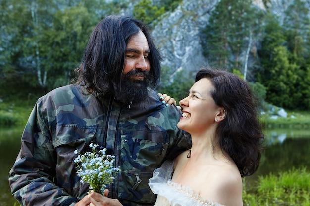 Hochzeitsfoto-shooting, braut und bräutigam, die für fotografen auf hintergrund des waldes und des flusses in wild aufwerfen.