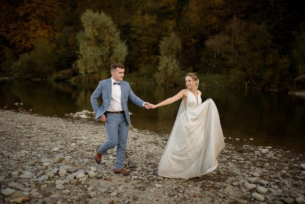 Hochzeitsfoto-sitzung der braut und des bräutigams in den bergen. fotoshooting bei sonnenuntergang.