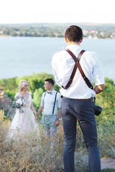 Hochzeitsfotograf fotografiert braut und bräutigam in der natur. hochzeitspaar auf fotoshooting. fotograf in aktion