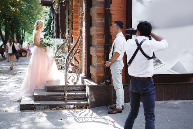 Hochzeitsfotograf fotografiert braut und bräutigam in der stadt. hochzeitspaar auf fotoshooting. fotograf in aktion