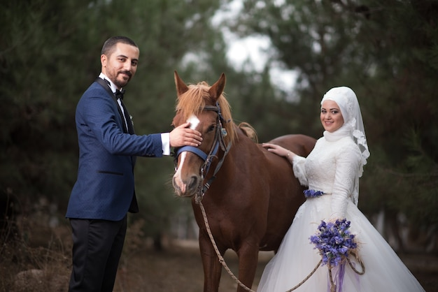 Hochzeitsfotos der jungen muslimischen braut und des bräutigams