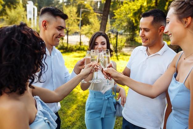 Hochzeitsgäste, die mit den gläsern anstoßen. gäste stoßen an und jubeln bei stilvoller feier.