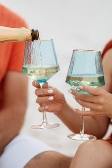 Hochzeitsgläser aus blauem glas mit champagner in der hand