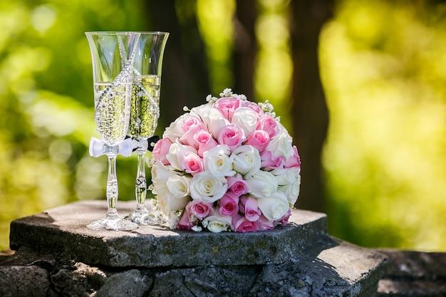 Hochzeitsgoldringe mit rosen und gläsern champagner