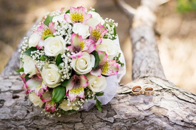 Hochzeitshintergrundblumenstrauß und -ringe auf holz.