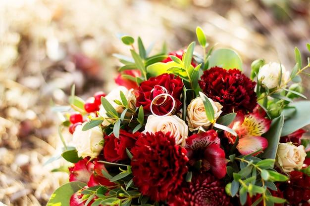 Hochzeitshintergrundblumenstrauß und -ringe.
