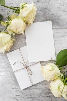 Hochzeitskarten mit rosen auf hölzernem hintergrund