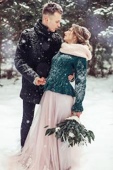 Hochzeitskaukasisches paar im wintersaisonporträt im freien. liebevolles süßes zartes paar in der liebe, die zusammen im auffälligen wald geht