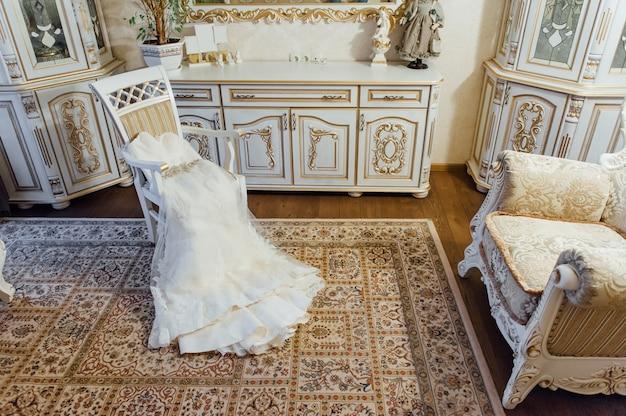 Hochzeitskleid auf einem stuhl im zimmer liegend
