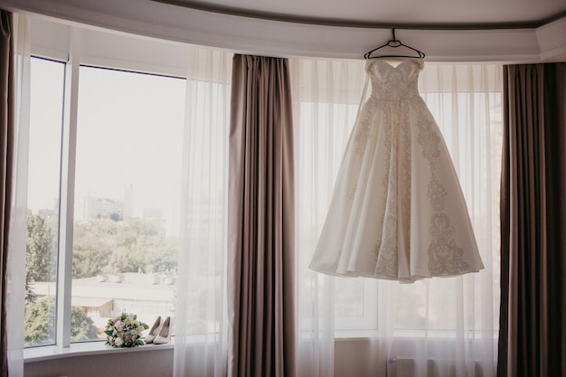 Hochzeitskleid auf kleiderbügel nahe fenster im brautraum