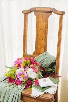 Hochzeitskleid; bibel; blumenstrauß und eheringe auf holzstuhl in der nähe des vorhangs