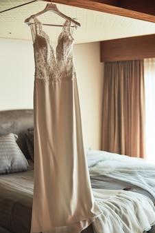 Hochzeitskleid, das an der decke in einem luxushotelzimmer hängt.