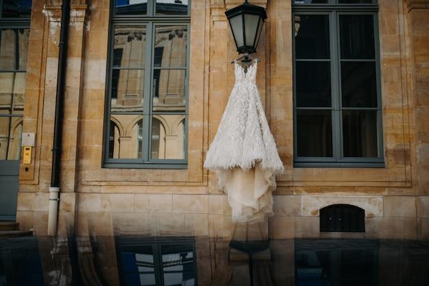 Hochzeitskleid, das an der straßenlaterne hängt