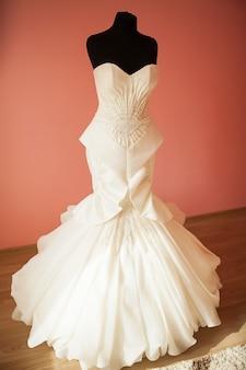 Hochzeitskleid, das an einem mannequin in einem raum der braut an ihrem hochzeitstag hängt
