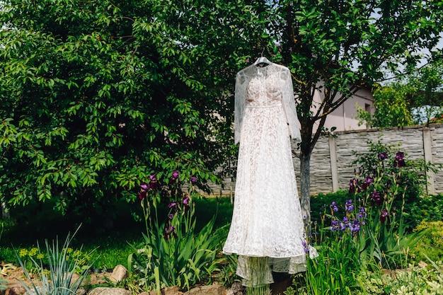 Hochzeitskleid der braut, die im grünen garten hängt