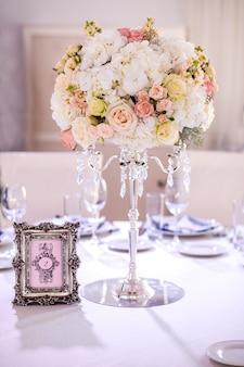 Hochzeitskomposition in form eines balls. pfirsich- und cremerosen, weiße hortensien auf einem kristallleuchter, fotorahmen, sitzplan für gäste der veranstaltung, hochzeitsdekoration