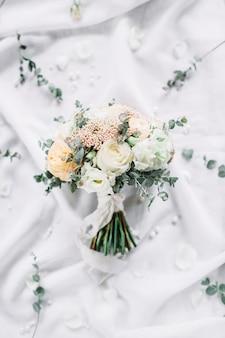 Hochzeitskomposition mit brautstrauß von eukalyptuszweigen, rosenblüten auf weißem textil
