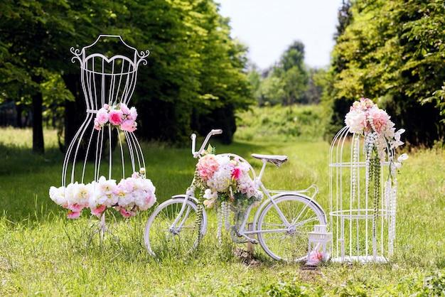 Hochzeitskomposition mit liebesstand, einem weißen fahrrad, frauenkleid in form und blumen