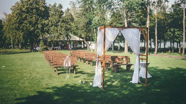Hochzeitskonzept mit einem hochzeitsbogen, der auf einem grünen rasen liegt