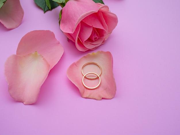 Hochzeitskonzept. schöne rosa rose auf rosa hintergrund mit zwei eheringen. speicherplatz kopieren.