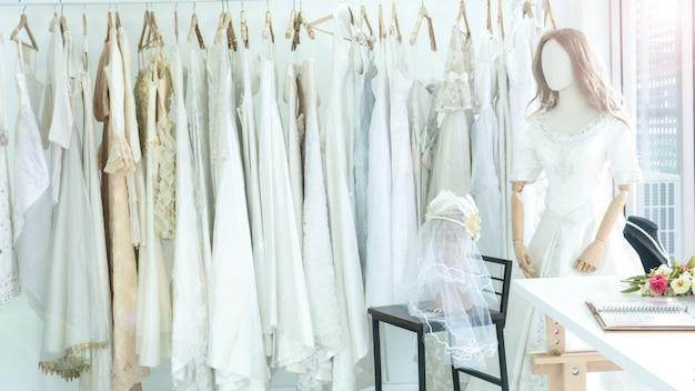 Hochzeitsmode verkleiden sich innenstudio mit hintergrund des hängenden weißen kleides der wäscheleine braut.