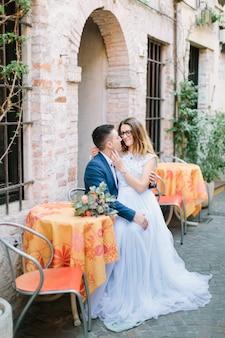 Hochzeitsmodeporträt des jungen paares mit nettem blumenstrauß, der am tisch der straßenbeschränkung in sirmione, italien sitzt