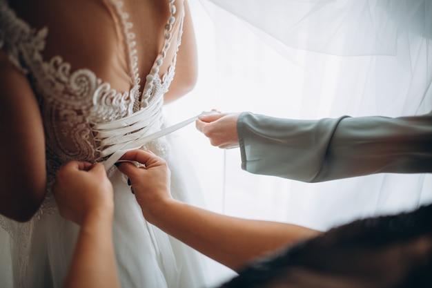 Hochzeitsmorgen. seitenansicht der braut im hochzeitskleid. brautjungfern bereiten braut für den hochzeitstag vor.