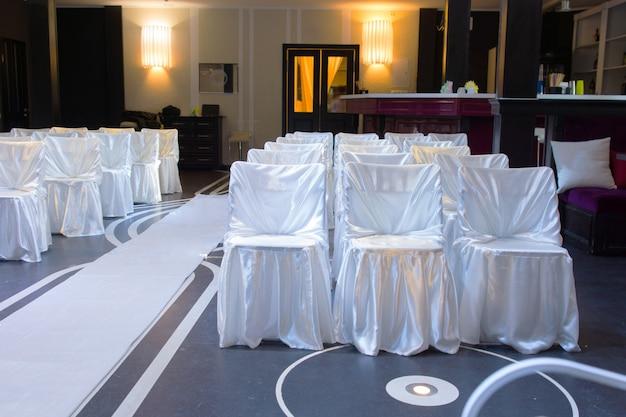 Hochzeitsort mit dekorativen weißen stühlen, die mit stoff zusammengebunden sind, neben einem weißen gang auf einem blauen boden, der von der vorderseite des raumes aus leer betrachtet wird
