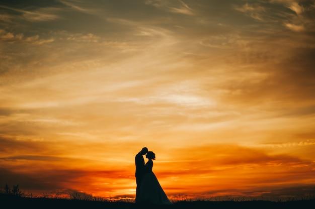 Hochzeitspaar auf dem hintergrund des sonnenuntergangs