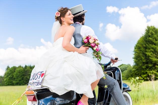 Hochzeitspaar auf dem motorroller gerade geheiratet