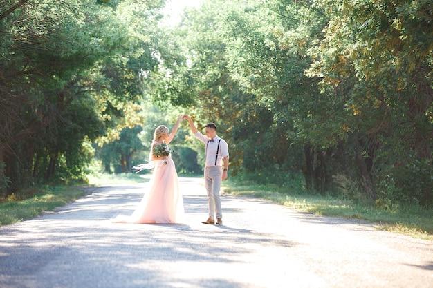 Hochzeitspaar auf der natur im sommertag. die braut und der bräutigam tanzen