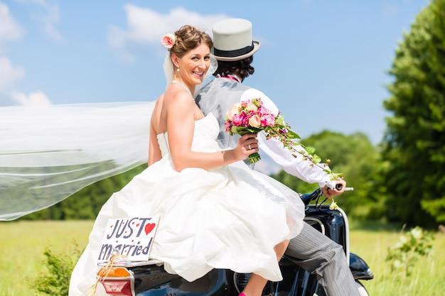 Hochzeitspaar auf motorroller gerade geheiratet