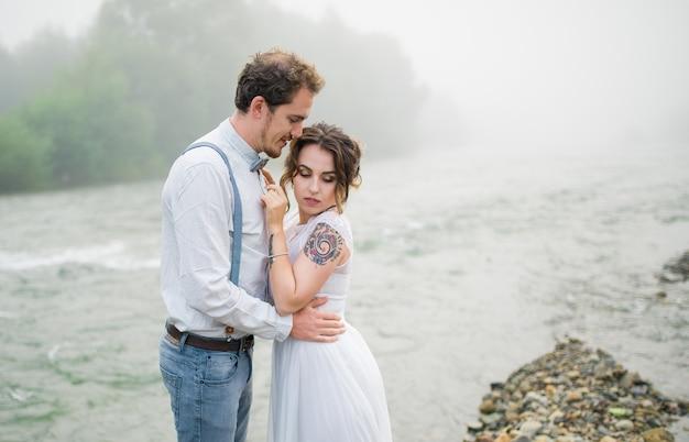 Hochzeitspaar, bräutigam und braut auf einem hintergrundgebirgsfluss