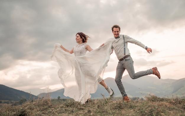 Hochzeitspaar, bräutigam und braut nahe hochzeitsbogen auf einem hintergrundberghügeln