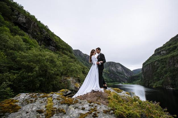 Hochzeitspaar, das auf einem felsen vor dem hintergrund des flusses steht