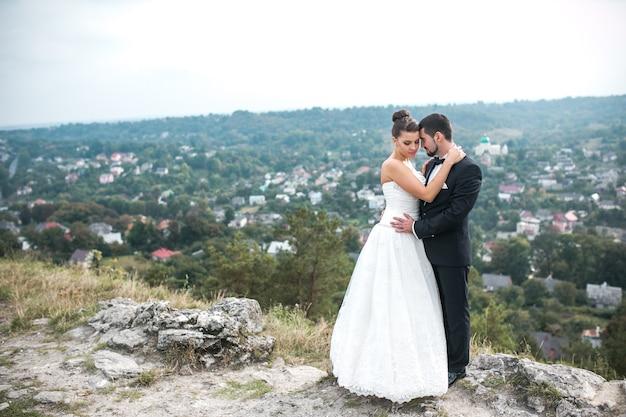 Hochzeitspaar, das für die kamera auf dem buckel aufwirft