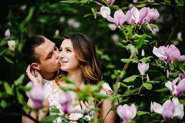 Hochzeitspaar, das im park auf dem hintergrund der rosa und lila blumen der magnolie und des grüns umarmt und küsst. hochzeitsort bei der zeremonie.