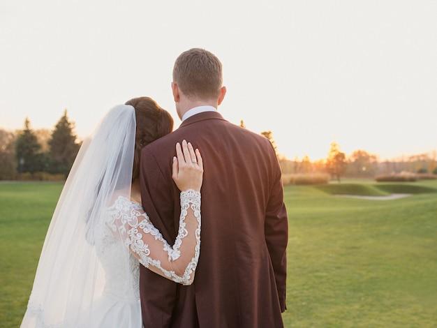 Hochzeitspaar frau und mann im hochzeitskleid und anzug beobachten den sonnenuntergang auf dem feld