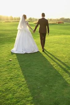 Hochzeitspaar frau und mann im hochzeitskleid und anzug zu fuß auf dem feld