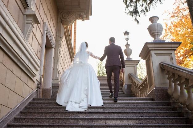 Hochzeitspaar frau und mann im hochzeitskleid und anzug zu fuß auf der schlosstreppe