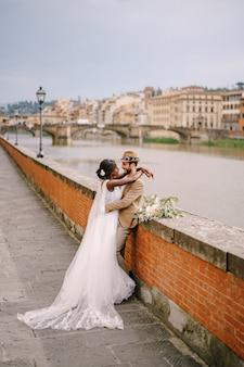Hochzeitspaar gemischter abstammung. hochzeit in florenz, italien. die afroamerikanische braut und der kaukasische bräutigam stehen am ufer des arno und blicken auf die stadt und die brücken.